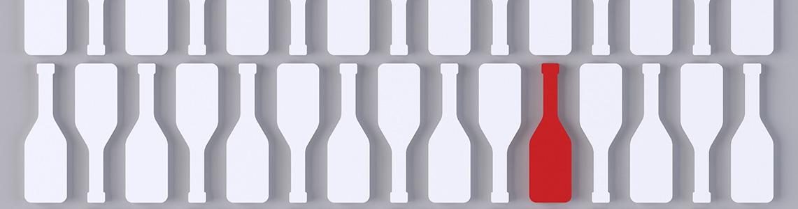 Eine rote Weinflasche unter vielen weißen Weinflaschen