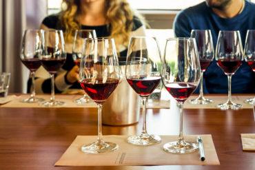 frau und Mann sitzen an Tisch. Vor ihnen stehen Rotweingläser | Silkes Weinkeller