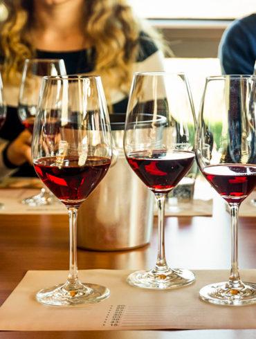 frau und Mann sitzen an Tisch. Vor ihnen stehen Rotweingläser   Silkes Weinkeller