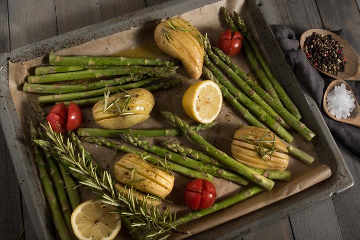 Grüner Spargel für die Zubereitung mit Zutaten auf einem Backblech