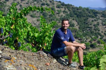 Der Winzer Albert Costa sitzt bei gutem Wetter in seinem Weinberg