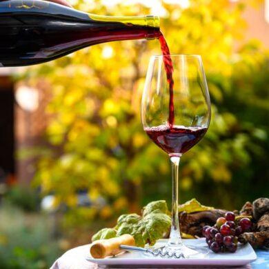 Glas steht auf Tisch im Garten und wird mit Rotwein befüllt.