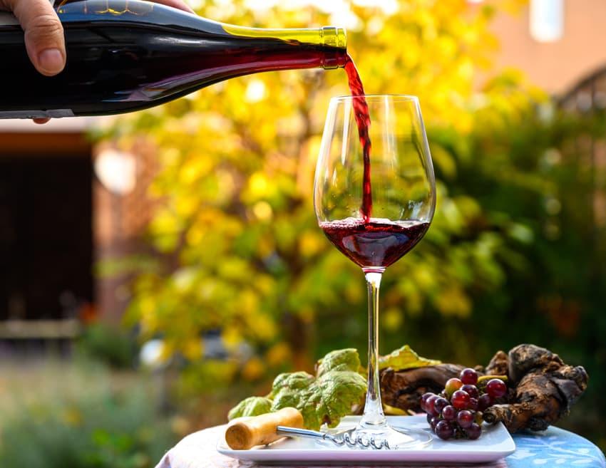 Zwei Rotweinflaschen und ein Glas auf braunem Holztisch