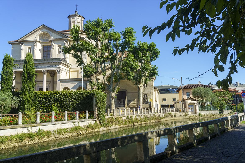 Norditalien: Weißes Gebäude hinter Palmen und Fluss