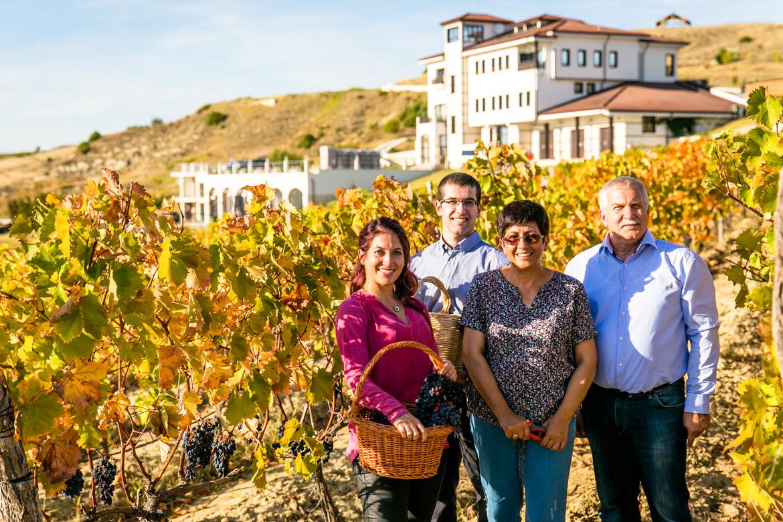 Vier Leute stehen vor Weinberg und Haus - Silkes Weinkeller