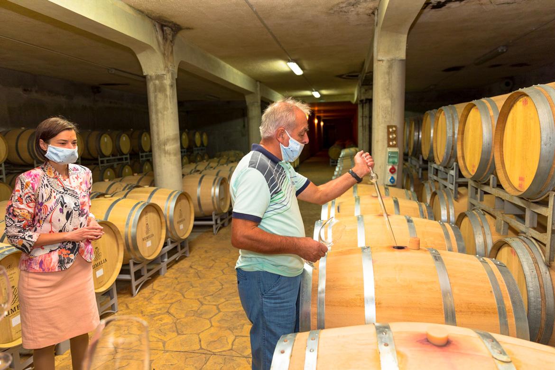 Frau und Mann vor Holzfässern - Silkes Weinkeller