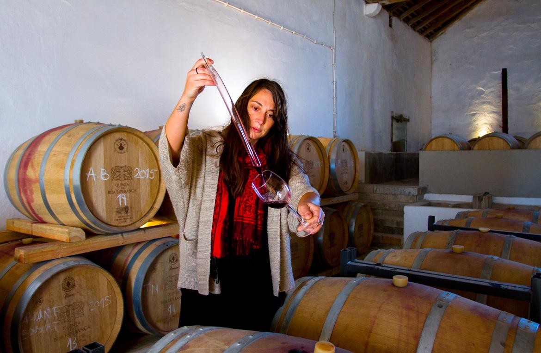 Frau füllt Rotwein im Weinkeller ins Glas