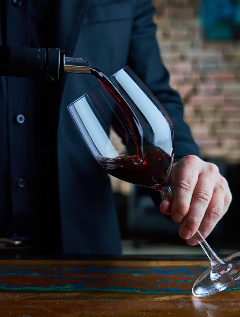 Mann schenkt Rotwein in Glas ein
