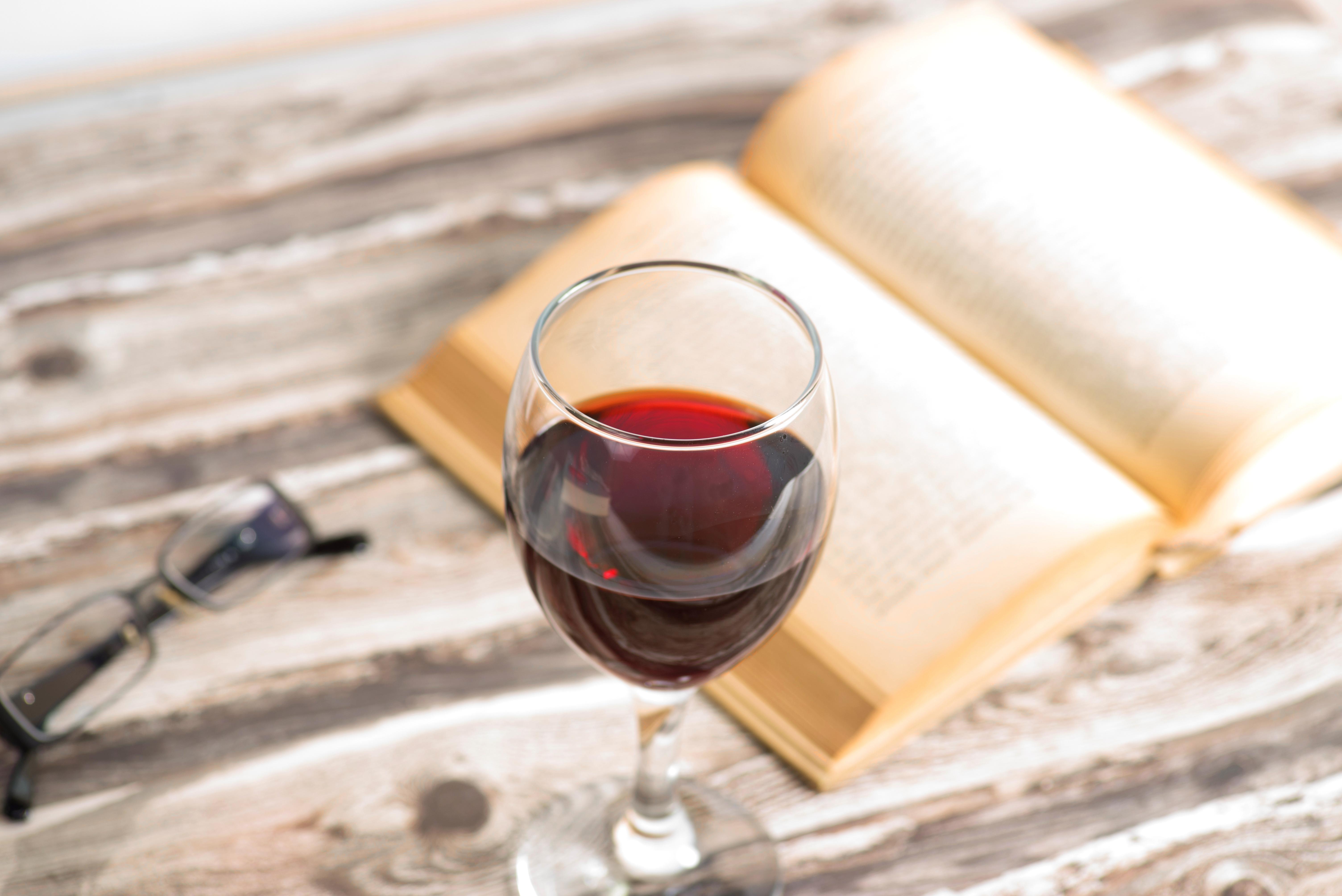 Glas Rotwein und Buch auf Tisch