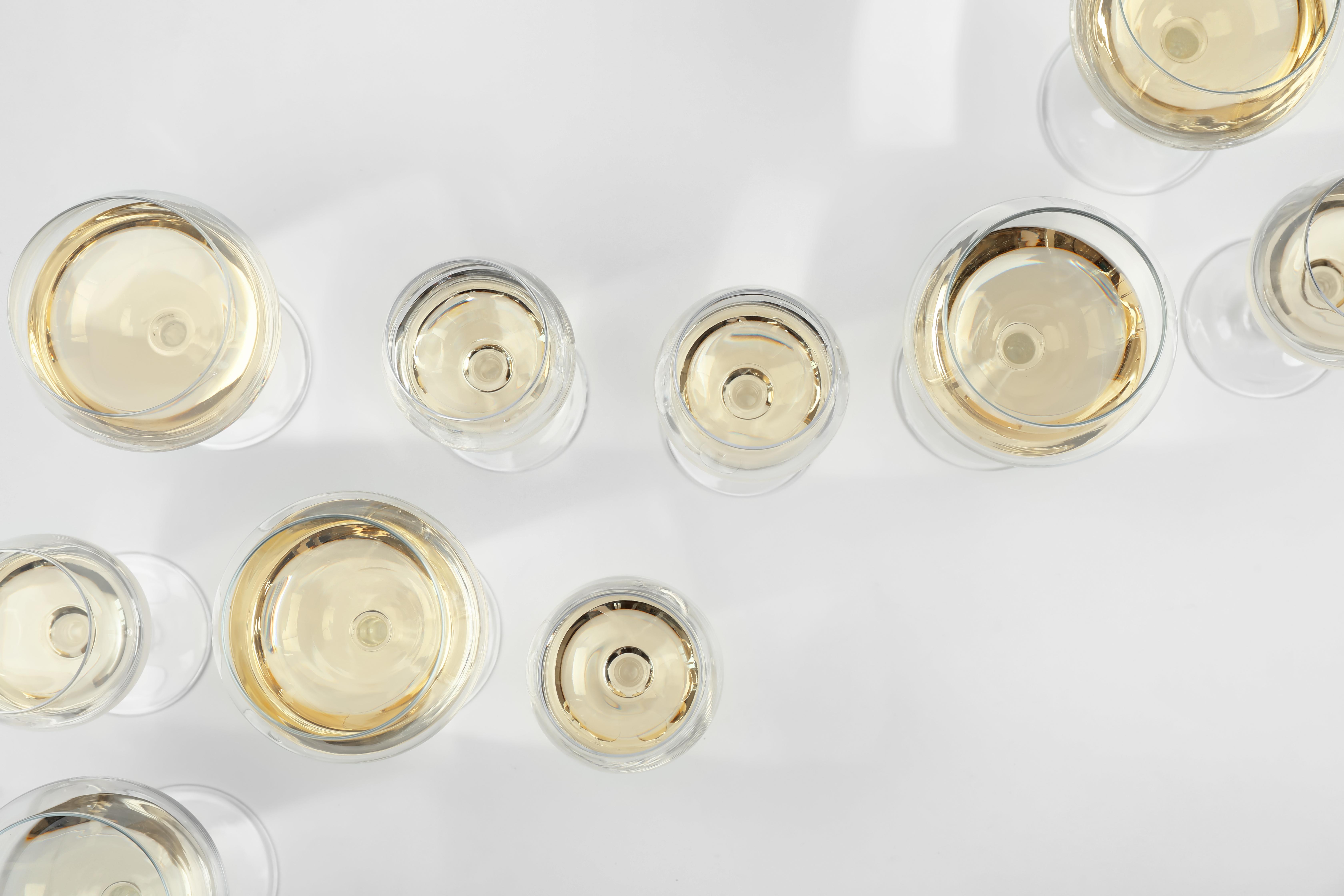 verschiedene Weingläser gefüllt mit Weißwein