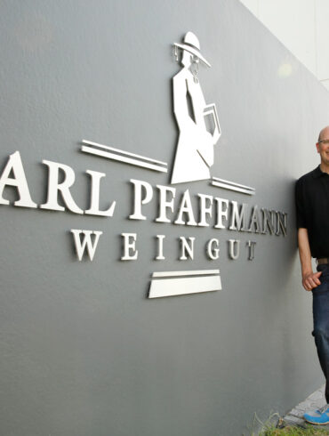 Mann neben grauen Wand stehend