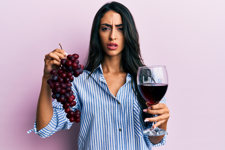 Frau mit Weintrauben und Rotweinglas in den Händen