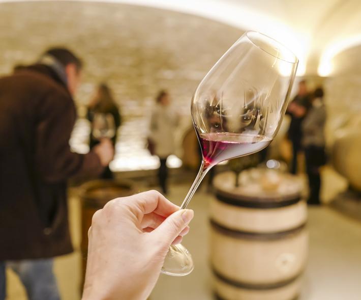 Hand mit Weinglas und Fässern im Hintergrund