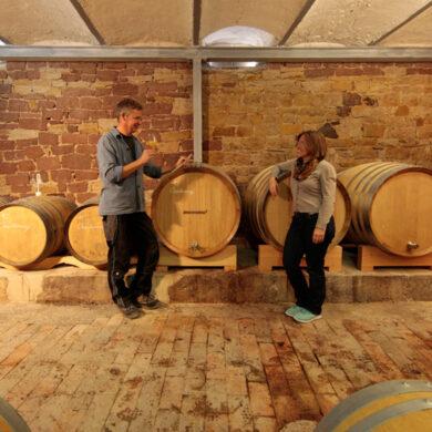 Zwei Menschen vor Weinfässern stehend