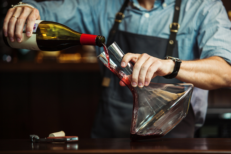 Mann beim Wein einschenken in Karaffe