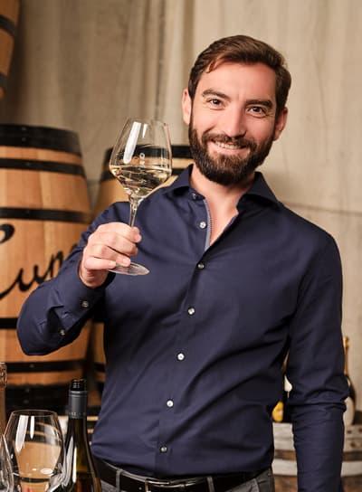 Mann mit blauem Hemd hält Weinglas