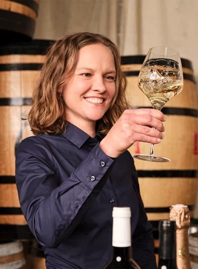Frau mit blauem Hemd hält Weinglas